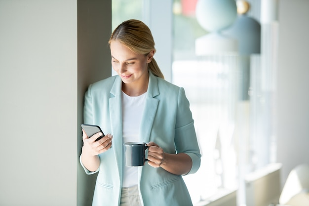 Giovane gestore di ufficio mobile che legge il messaggio o la notifica nello smartphone mentre beve in pausa