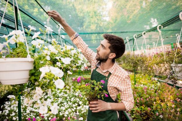 Giovane giardiniere allegro bello che sorride, prendendosi cura dei fiori