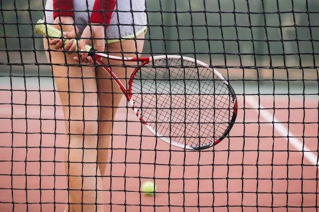 Giovane giocatore del primo piano di tennis sul campo