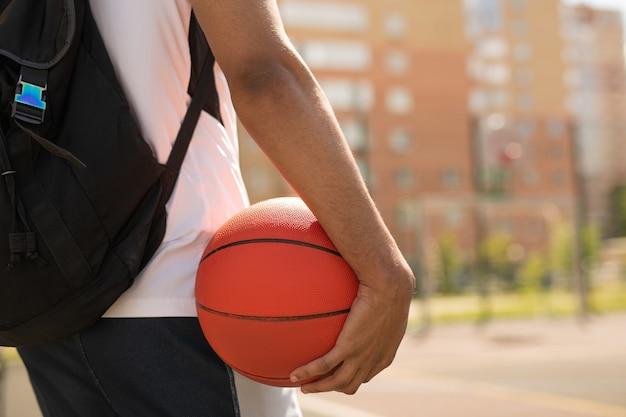 Giovane giocatore di basket con palla e zaino in piedi sul campo da giuoco prima dell'allenamento all'aperto