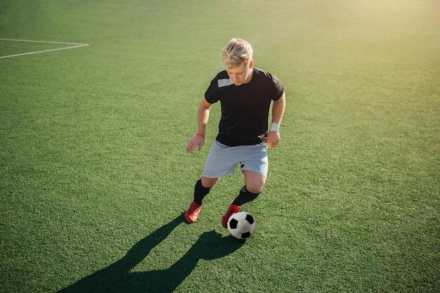Giovane giocatore di football americano biondo che gioca sul prato inglese verde fuori. sta per calciare la palla.