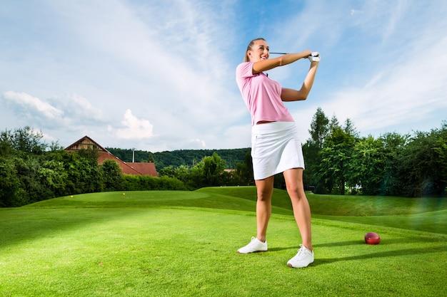 Giovane giocatore di golf femminile sul corso che fa l'oscillazione di golf