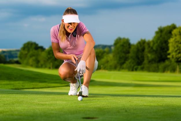 Giovane giocatore di golf femminile sul corso che mira al suo messo