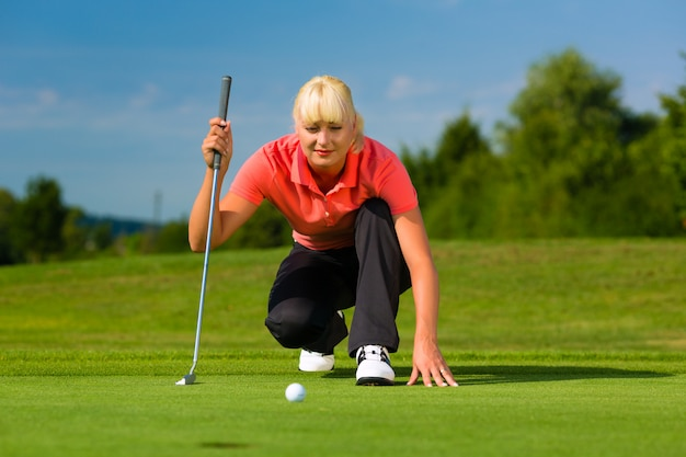 Giovane giocatore di golf femminile sul corso che tende a mettere