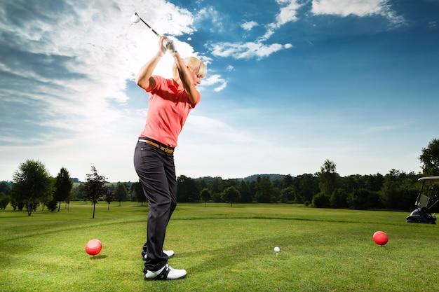 Giovane giocatore di golf in corso facendo swing golf