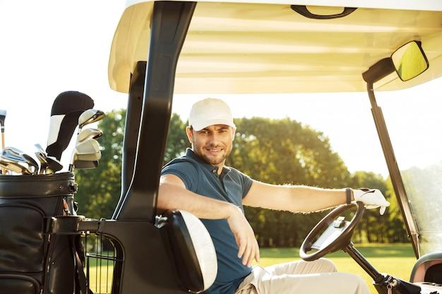 Giovane giocatore di golf maschio sorridente che si siede in un carrello di golf