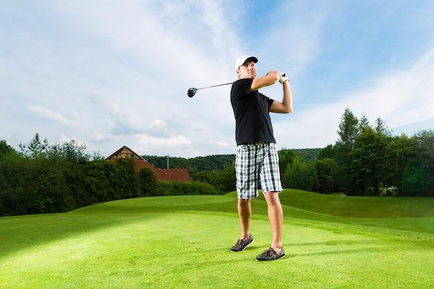 Giovane giocatore di golf sul corso che fa l'oscillazione di golf
