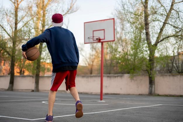 Giovane giocatore di pallacanestro che si prepara a dribblare all'aperto sulla corte dell'asfalto