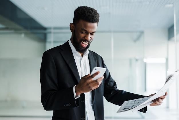 Giovane giornale afroamericano della lettura dell'uomo d'affari e parlare al telefono nel suo ufficio