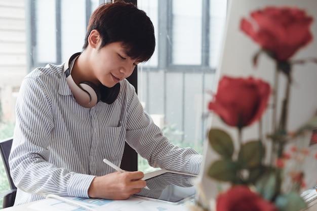 Giovane giovane impresa asiatica felice che si siede e che lavora alla compressa digitale