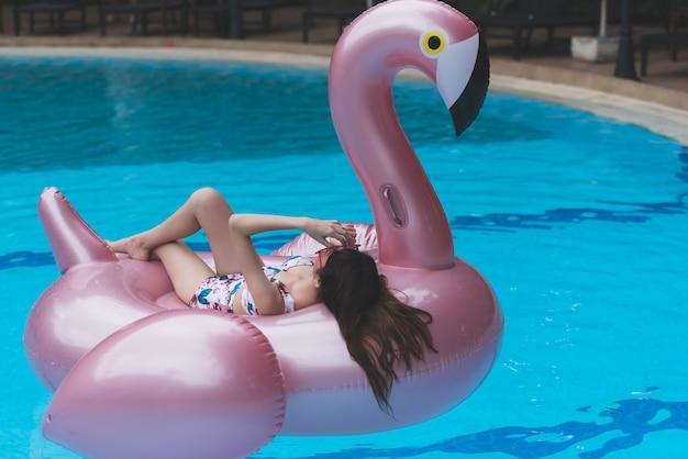 Giovane giro asiatico della donna sul cigno gonfiabile gigante nella piscina.