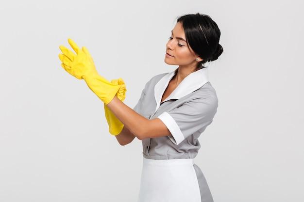 Giovane governante caucasica che indossa i guanti protettivi di pulizia, guardanti da parte