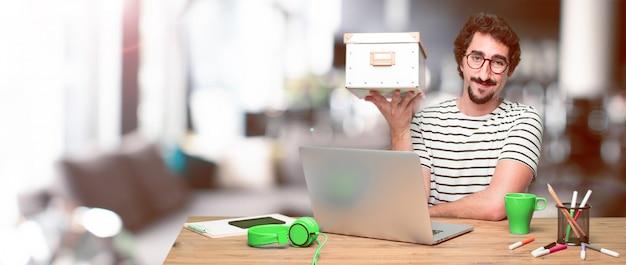 Giovane grafico pazzo su una scrivania con un computer portatile e con un
