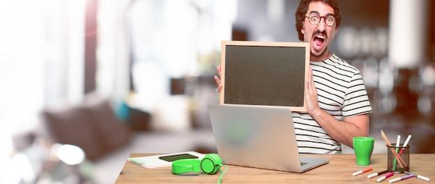 Giovane grafico pazzo su una scrivania con un computer portatile