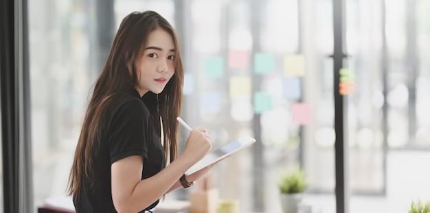 Giovane graphic designer femminile attraente che lavora al progetto
