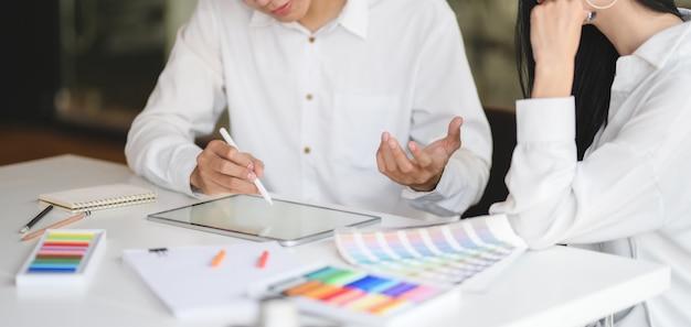 Giovane graphic designer professionista che lavora al loro progetto insieme a tablet in ufficio moderno