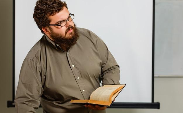 Giovane grasso con i vetri che tengono un libro