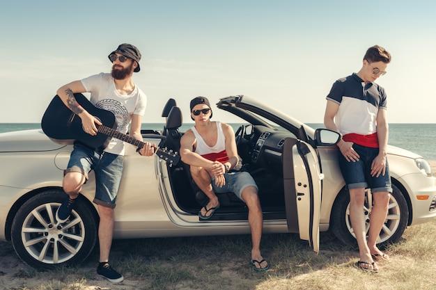 Giovane gruppo divertendosi sulla spiaggia che gioca chitarra
