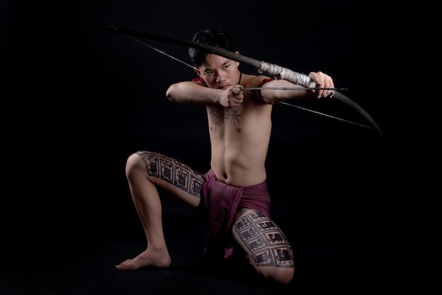 Giovane guerriero maschio della tailandia che posa in una posizione di combattimento con un arco