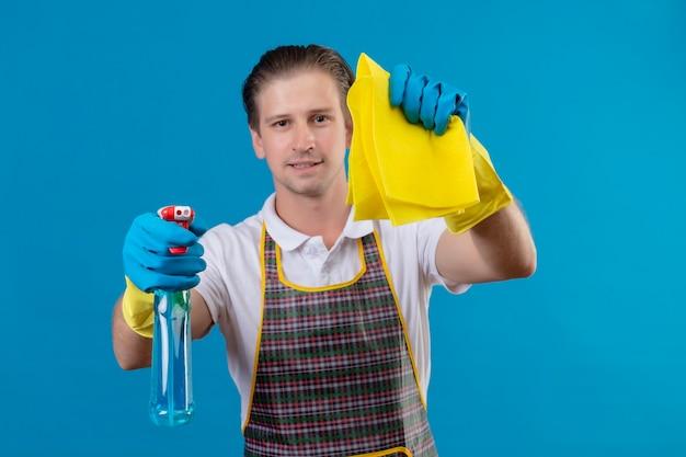 Giovane hansdome uomo che indossa un grembiule e guanti di gomma tenendo la pulizia spray e tappeto