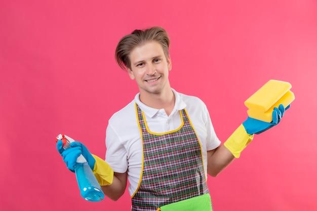 Giovane hansdome uomo che indossa un grembiule e guanti di gomma tenendo spray per la pulizia e spugna con un grande sorriso sul viso felice e positivo in piedi oltre il muro rosa