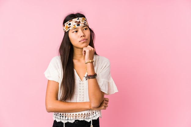 Giovane hippy cinese che guarda lateralmente con espressione dubbiosa e scettica