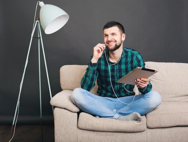 Giovane hipster bello uomo seduto sul divano a casa tenendo tablet, ascoltando musica sugli auricolari, parlando online, felice, sorridente, camicia a scacchi verde, tempo libero, riposo