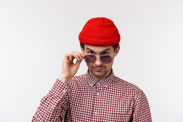 Giovane hipster hipster scettico e dubbioso con baffi, berretto rosso, sguardo da sotto la fronte incredulo, occhiali da decollo per guardare seriamente alla persona strana