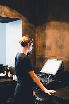 Giovane hostess in piedi vicino al registratore di cassa