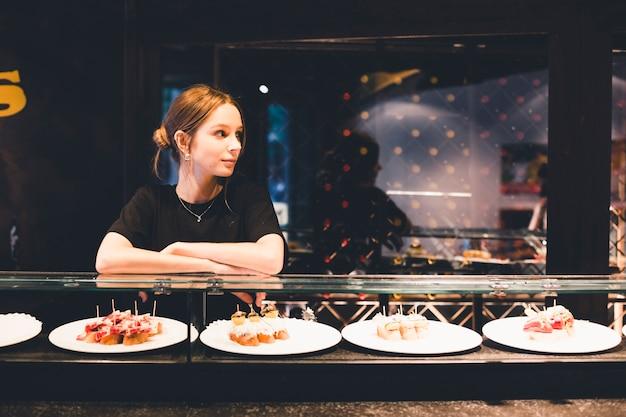 Giovane hostess vicino a tartines