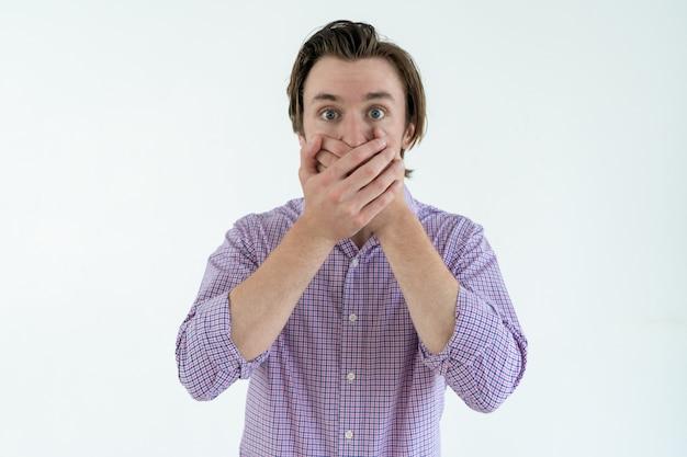 Giovane imbarazzato che copre la bocca con entrambe le mani. concetto di imbarazzo.