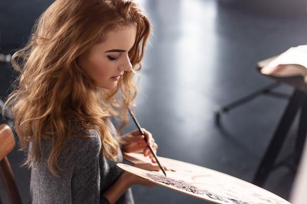 Giovane immagine della pittura dell'artista femminile in studio