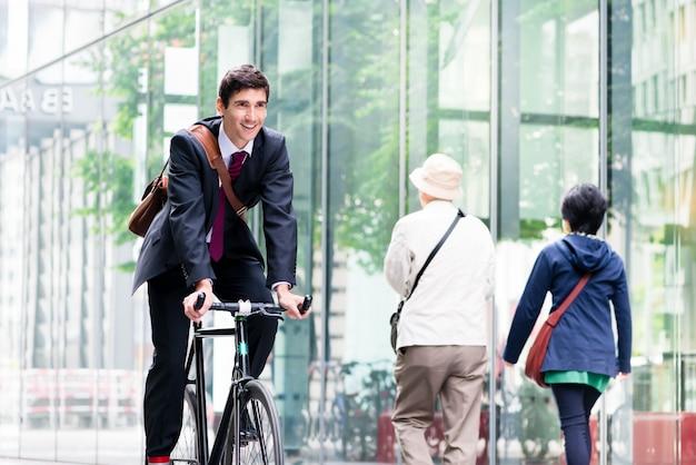 Giovane impiegato allegro che guida una bicicletta pratica a berlino