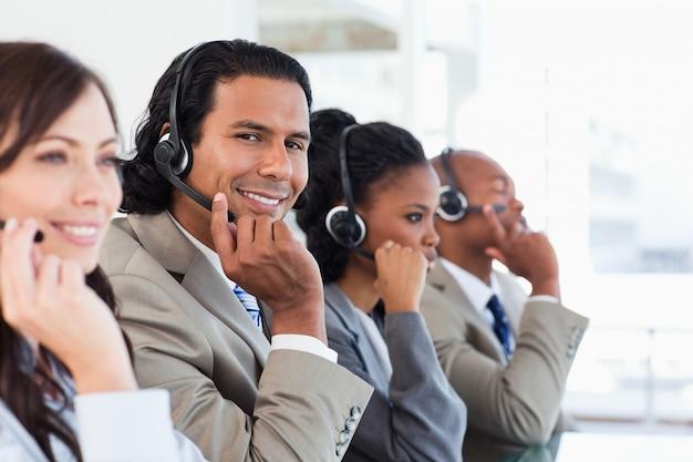 Giovane impiegato del centro di chiamata che lavora fra la sua squadra