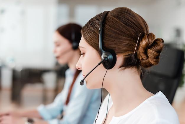 Giovane impiegato di concetto professionale con una cuffia avricolare che risponde in un call center