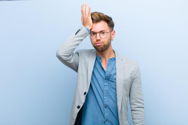 Giovane imprenditore alzando il palmo alla fronte pensando oops, dopo aver fatto uno stupido errore o aver ricordato, sentendosi stupido