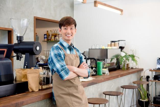 Giovane imprenditore asiatico allegro dell'uomo in caffetteria