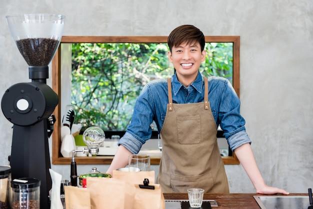 Giovane imprenditore asiatico sorridente alla contro bancone della caffetteria