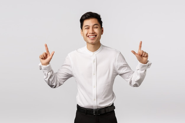 Giovane imprenditore asiatico sorridente allegro con la camicia bianca che indica su
