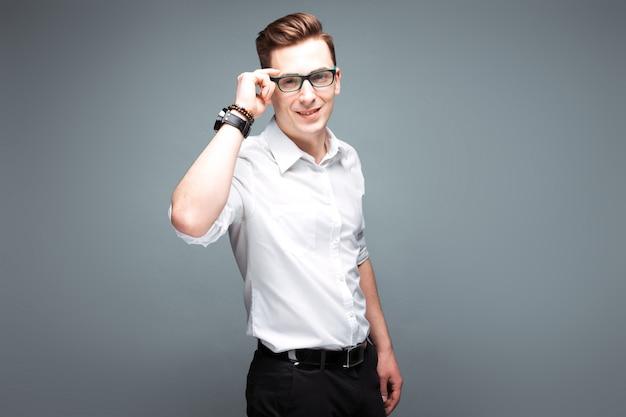 Giovane imprenditore attraente in costoso orologio, occhiali neri e camicia bianca