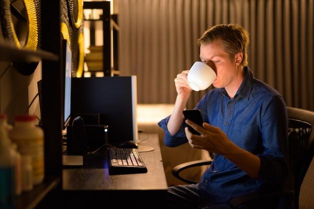 Giovane imprenditore bello bere caffè e utilizzare il telefono mentre si fa gli straordinari a casa