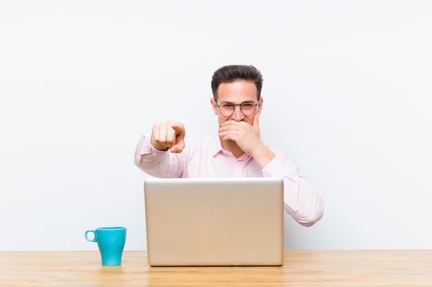 Giovane imprenditore bello ridere di te, indicando e prendendo in giro o deridendoti