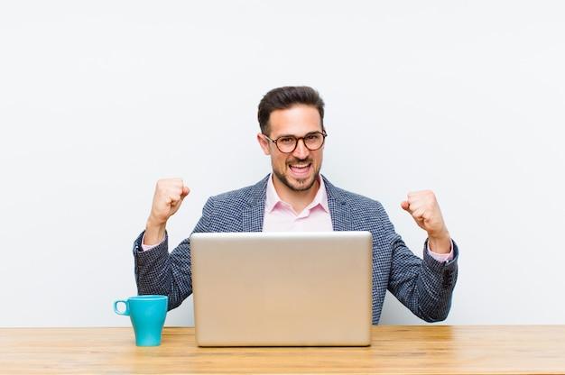 Giovane imprenditore bello sentirsi felici, positivi e di successo, celebrando la vittoria, i risultati o la buona fortuna