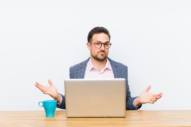 Giovane imprenditore bello sentirsi perplesso e confuso, incerto sulla risposta o decisione corretta, cercando di fare una scelta