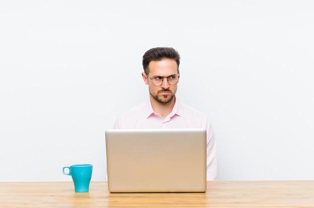 Giovane imprenditore bello sentirsi triste, arrabbiato o arrabbiato e guardando al lato con un atteggiamento negativo, accigliato in disaccordo