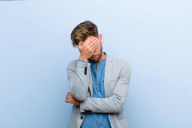 Giovane imprenditore cercando stressato, vergogna o sconvolto, con un mal di testa, che copre il viso con la mano contro il blu