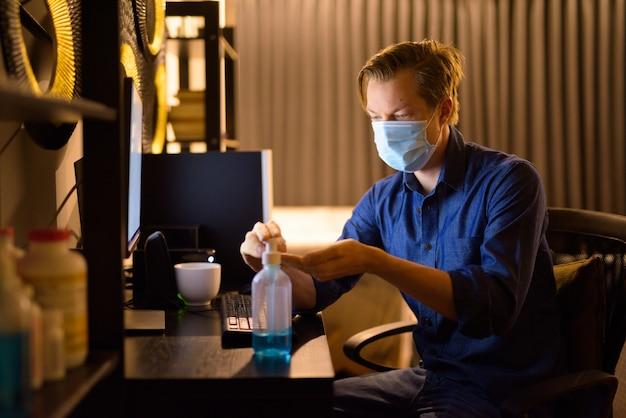 Giovane imprenditore con maschera utilizzando disinfettante per le mani mentre si lavora da casa durante la notte