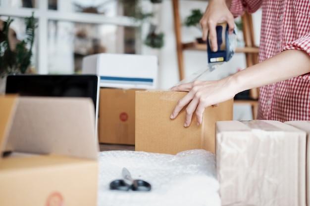 Giovane imprenditore di avvio piccolo imprenditore che lavora a casa, imballaggio e consegna situazione.
