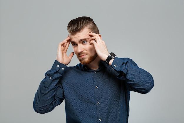 Giovane imprenditore di successo con mal di testa sul muro grigio.