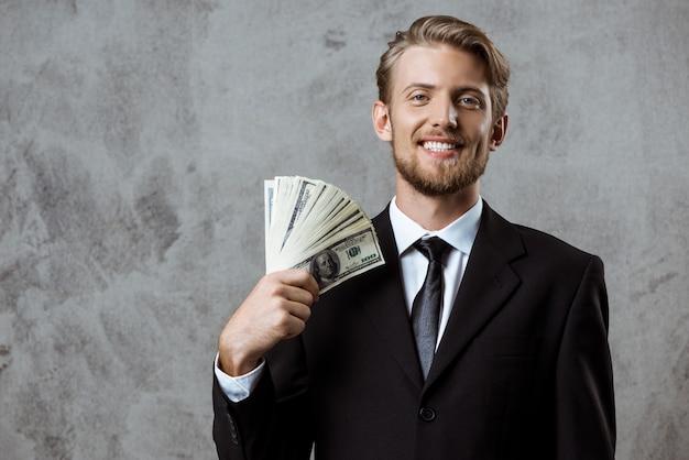 Giovane imprenditore di successo sorridendo, tenendo i soldi